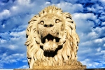 A lion guards the Buda side of the Chain Bridge in Budapest, Hungary