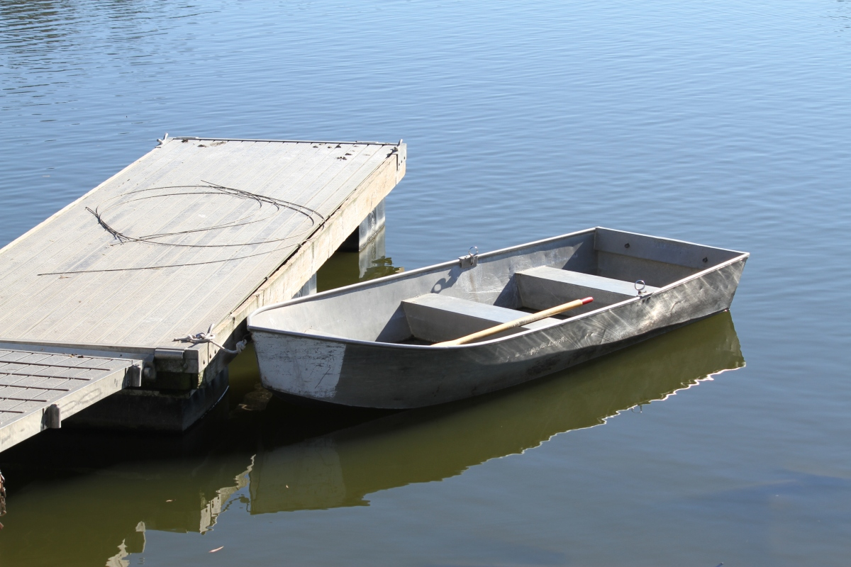 A parks workboat lays alongside a small dock on the calm lake