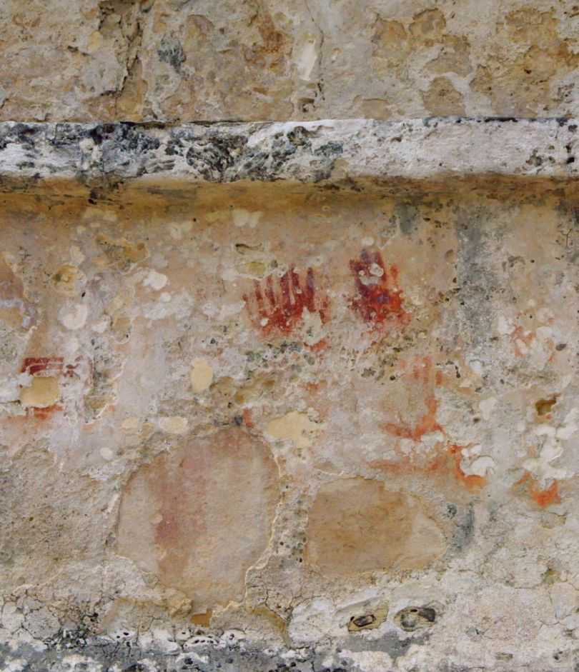 Handprints decorate an ancient Mayan wall in the old city of Tulum in Mexico