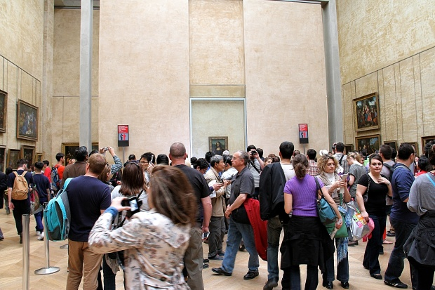The crowds pressing around the Mona Lisa. The actual painting is behind glass.  It take about 10 minutes to work you way up to the front to get close enough for a picture.
