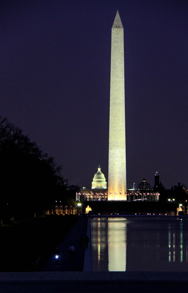 The Washington Monument  casting a light on the reflecting pool.  Capitol in the background.