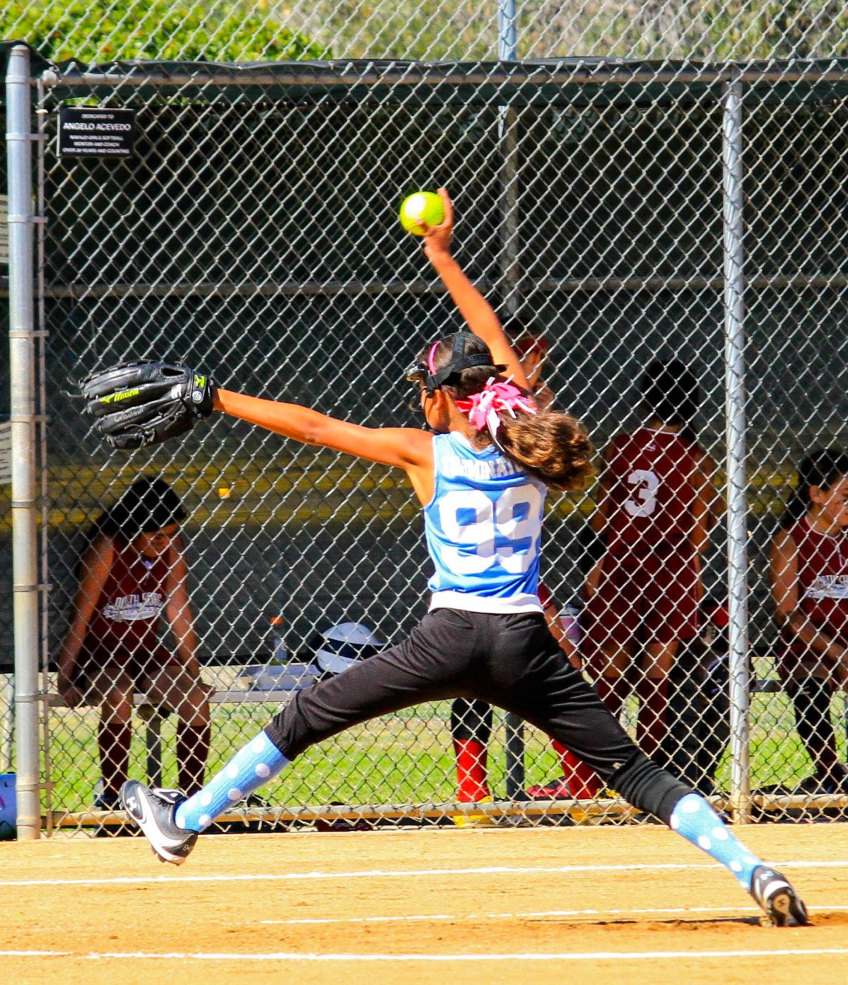A girl's softball pitcher winds up for a fast ball