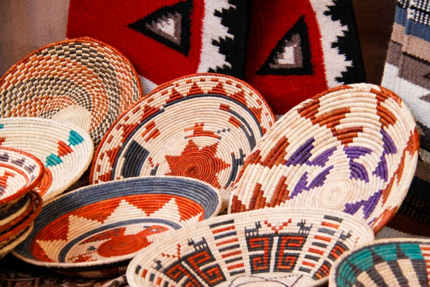 Traditional Indian baskets and plates woven out of desert grasses and stick and bushes.  The blood red coloring used to decorate the baskets reminds Kongo of all the blood in the street from the accident just a block up the road where the firemen are trying desperately to save the life of the lover of the woman in the straw hat.