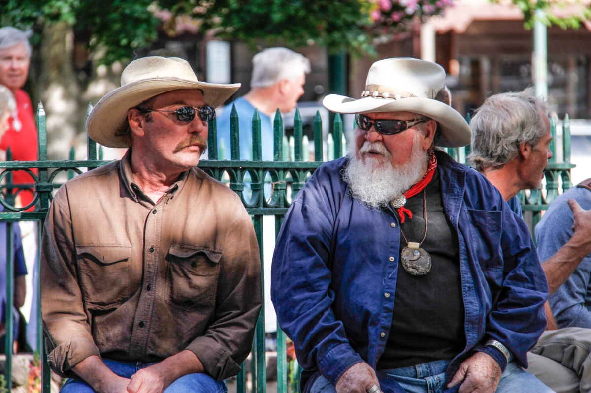 The story behind these two cowboys is easy to imagine.  They are remembering former glory days on the range as they settle into comfortable retirement.  Or, more likely, they are comparing notes about the two single women just off camera who were dancing with each other to the music of a grassroots band called something like Felix de los Gatos.
