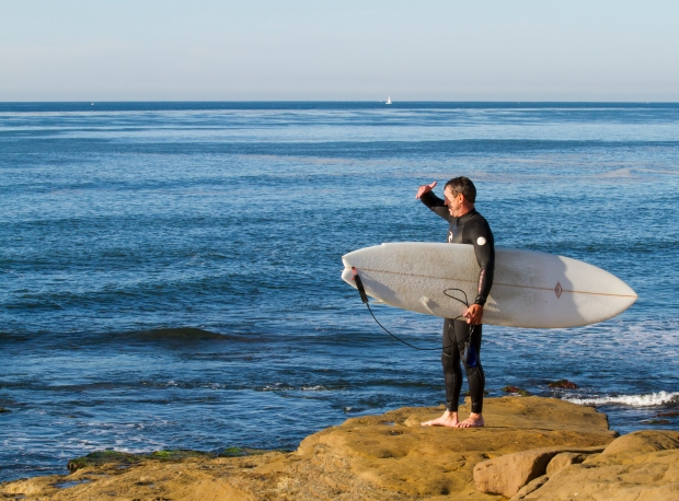 A surfer checks out the waves off Sunset Cliffs before climbing down the rocks to catch the surf.