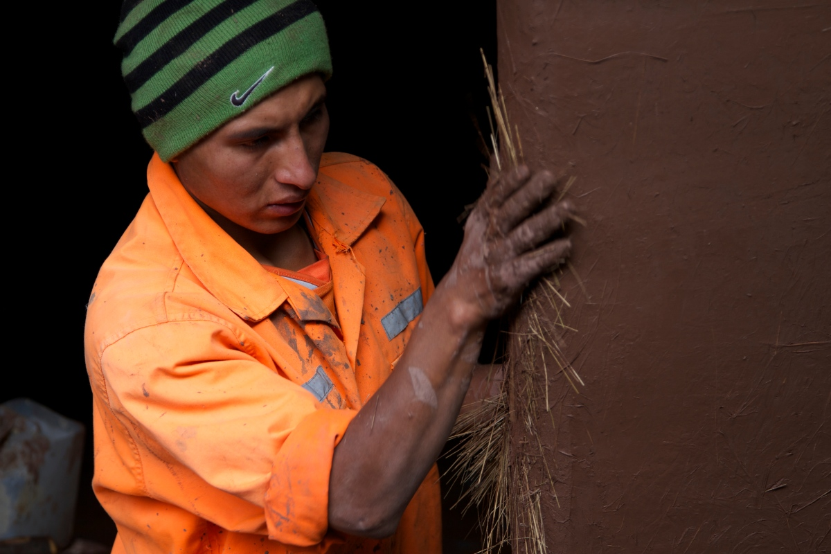 The buildings at the llama farm are made of adobe and this worker was putting the finishing touches on a new addition to the complex.  Kongo liked this image because it emphasizes how adobe is made with just mud and straw.