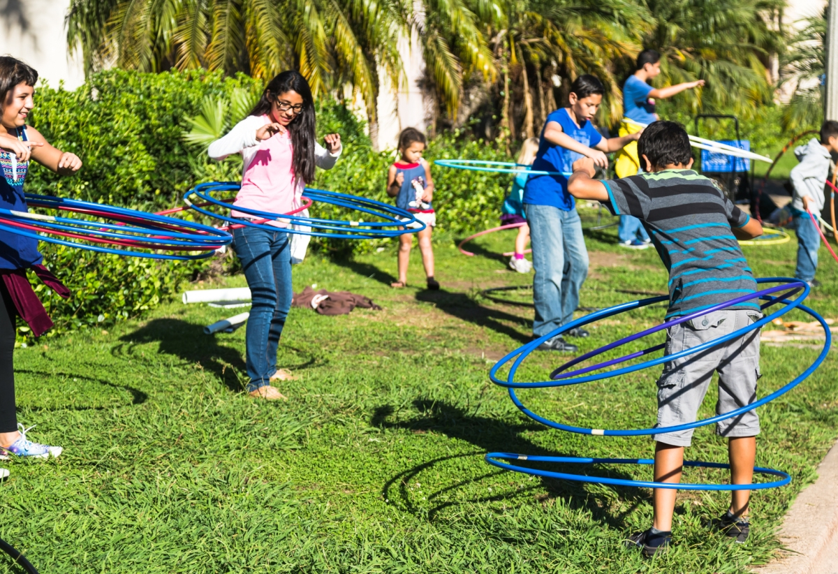 Children play with hula hoops along the Prado